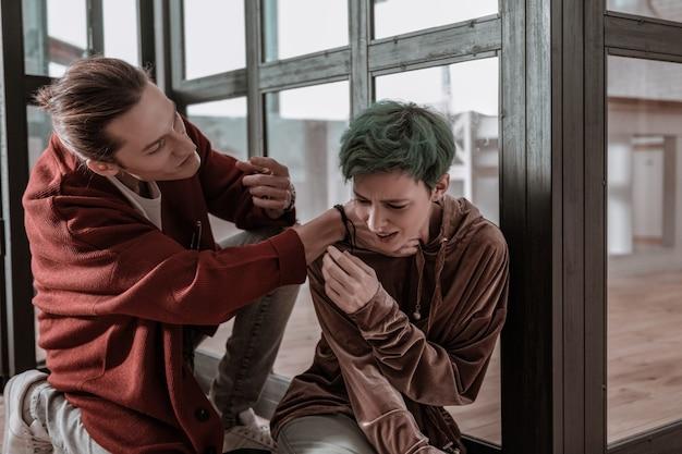 Hals vasthouden. boze en agressieve jonge man die de nek van zijn hulpeloze huilende vrouw vasthoudt