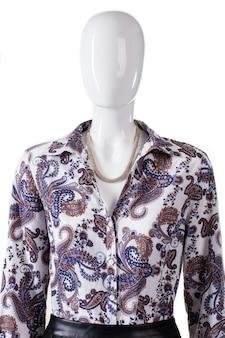 Halsband en overhemd op etalagepop. dames losgeknoopt overhemd met ketting. bloemmotief kledingstuk en sieraden. luxe uitstraling voor jonge dames.