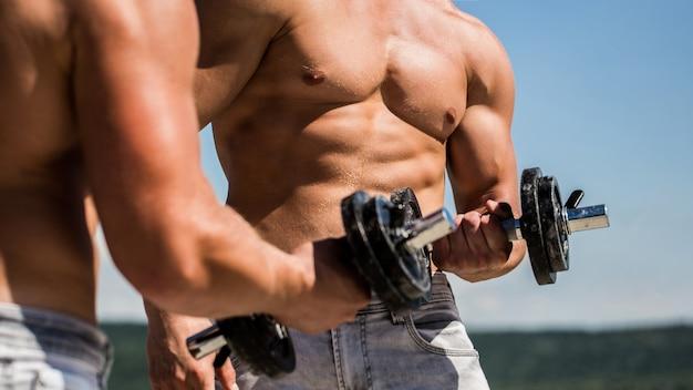Halter. gespierde bodybuilder jongens, oefeningen met halters