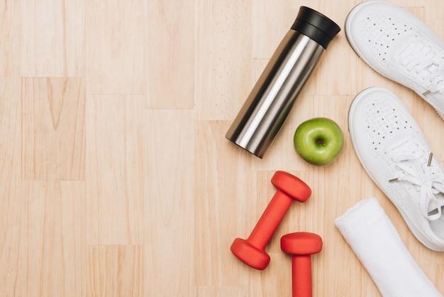 Halters, fles water en springtouw op blauwe achtergrond. bovenaanzicht. fitness, sport en gezonde levensstijl concept.
