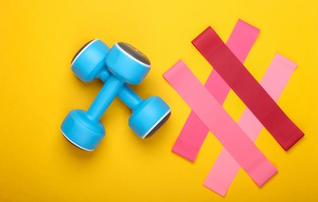 Halters met fitnesselastiekjes op een gele achtergrond. bovenaanzicht, plat gelegd