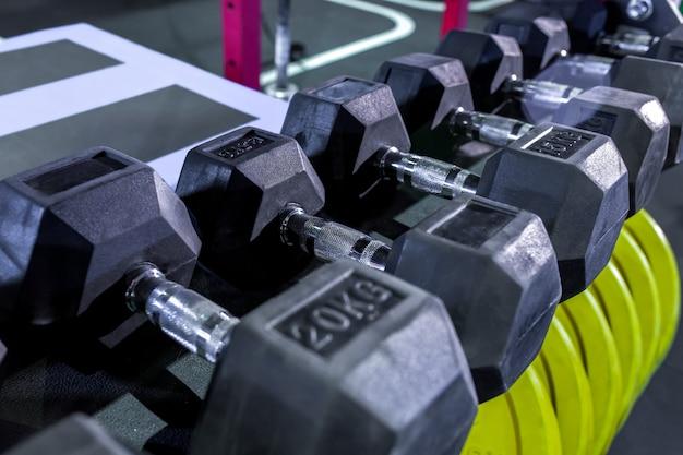 Halters, pannenkoeken en gewichten liggen op de planken. sportschool. apparatuur voor gym