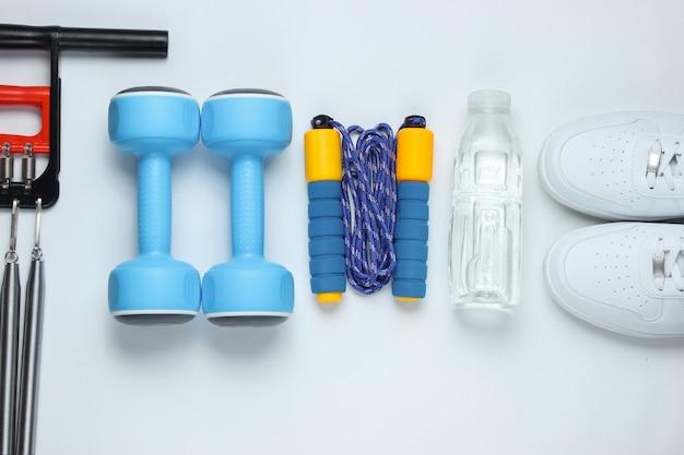 Halters, sportschoenen, springtouw, fles water, expander. sportuitrusting op witte achtergrond. bovenaanzicht