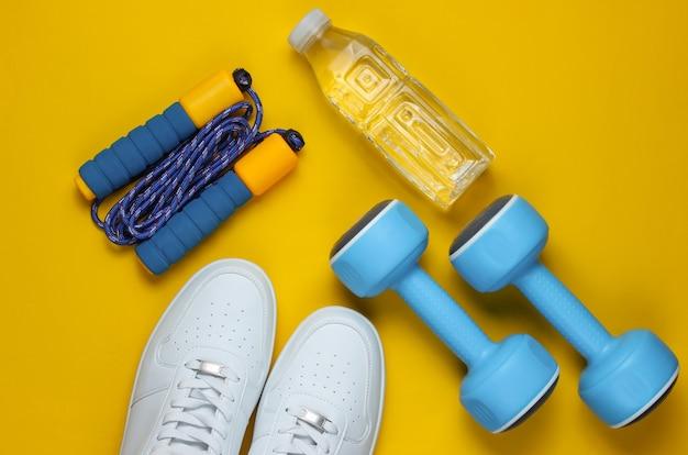 Halters, sportschoenen, springtouw, fles water. sportuitrusting op gele achtergrond. kopieer ruimte. bovenaanzicht