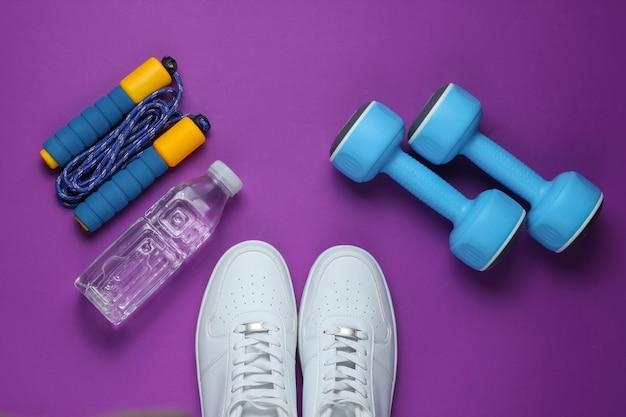 Halters, sportschoenen, springtouw, fles water. sportuitrusting op paarse achtergrond. kopieer ruimte. bovenaanzicht