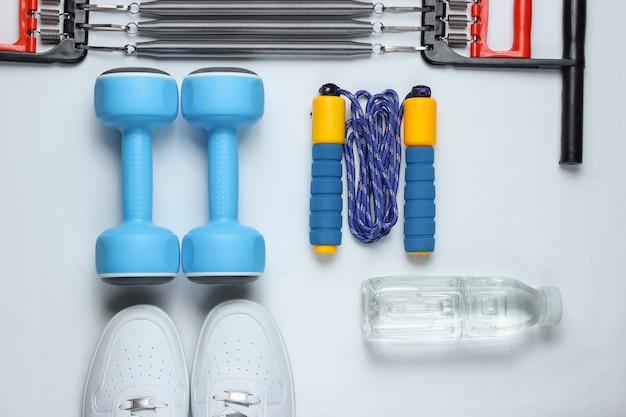 Halters, sportschoenen, springtouw, fles water. sportuitrusting op witte achtergrond. bovenaanzicht