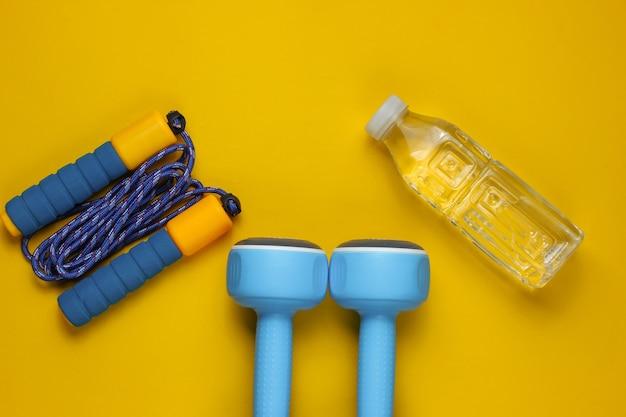 Halters, springtouw, fles water. sportuitrusting op gele achtergrond. kopieer ruimte. bovenaanzicht