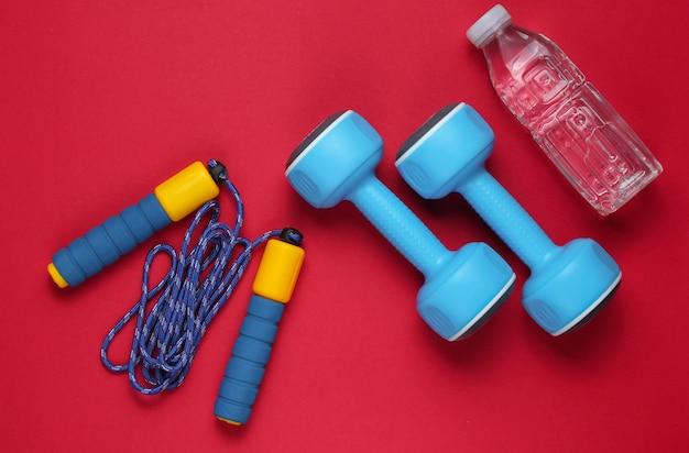 Halters, springtouw, fles water. sportuitrusting op rode achtergrond. kopieer ruimte. bovenaanzicht