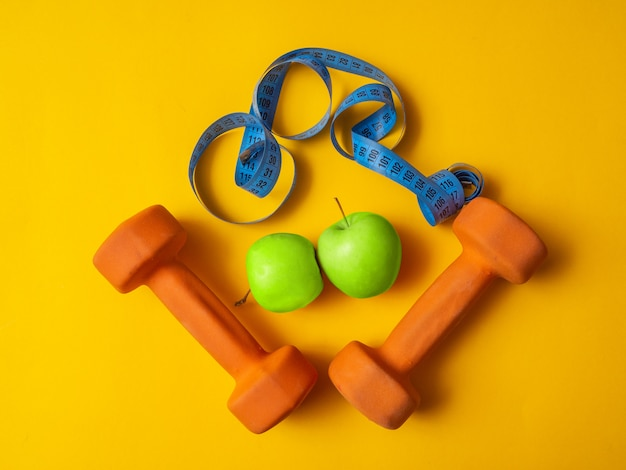 Halters voor fitness, appels en meetlint op een gele achtergrond. concept van gewichtsverlies. flatlay, copyspace.