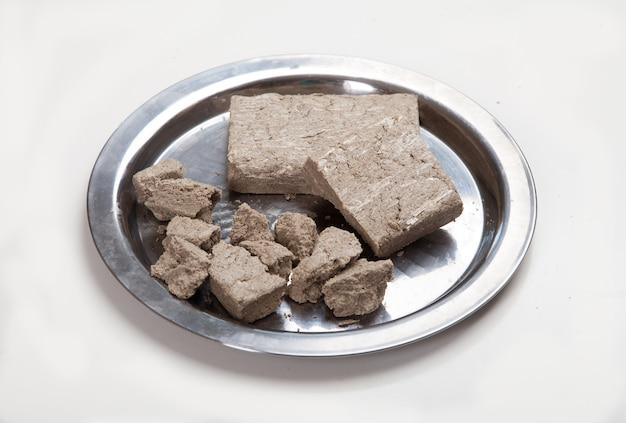 Halva in briketten en in grote stukken ligt op een metalen plaat op een witte achtergrond.