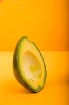 Halve avocado die op gele achtergrond wordt geïsoleerd