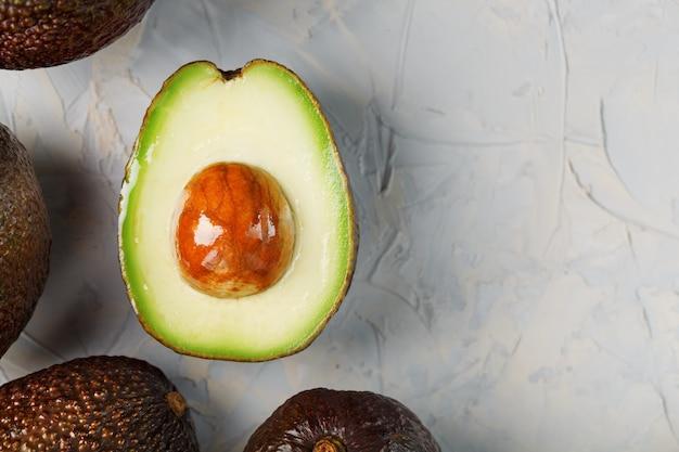 Halve avocado's met hele hass-vruchten op een oppervlak van grijs beton