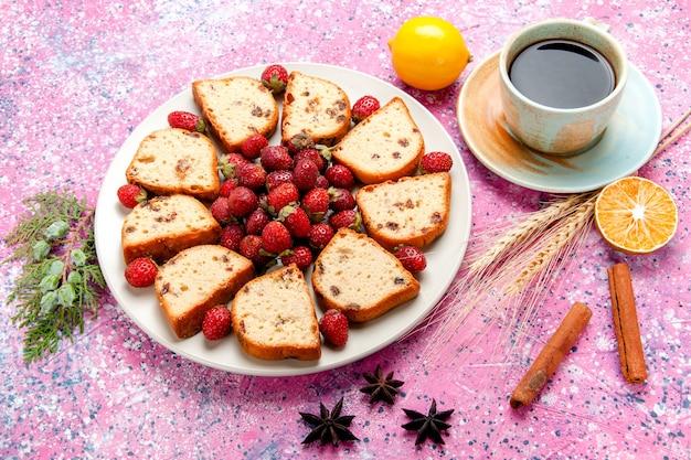 Halve bovenaanzicht cake plakjes met verse aardbeien en kopje koffie op roze bureau cake bakken zoete biscuit kleur taart suiker koekje