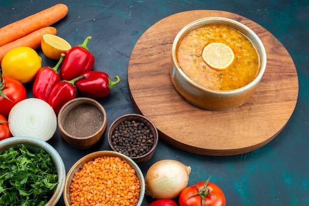 Halve bovenaanzicht groentesoep met verse groenten greens en kruiden op donkerblauw bureau.