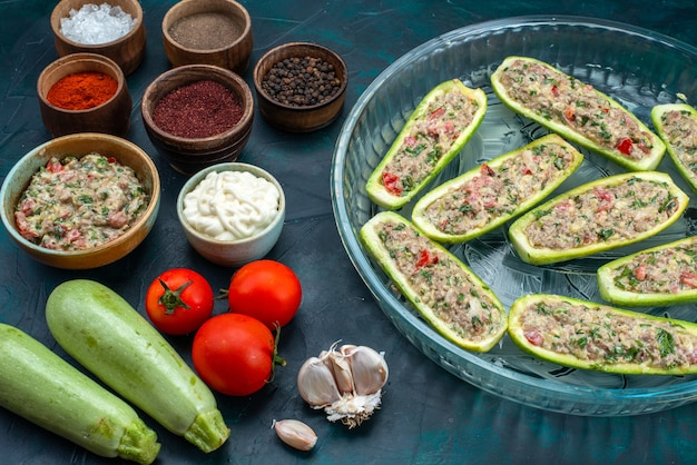 Halve bovenaanzicht rauwe pompoenen met pittig gehakt samen met groenten op donkerblauw bureau.