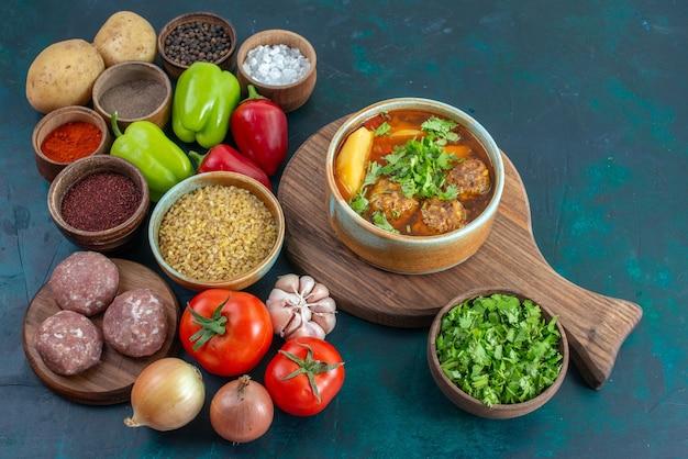 Halve bovenaanzicht verse groenten met kruiden, vlees soep en greens op donkerblauwe groentes van de de maaltijdschotel van het bureaugroente voedsel