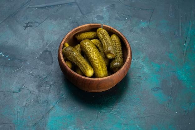Halve bovenaanzicht zoute augurken in ronde bruine pot op donkerblauw bureau.