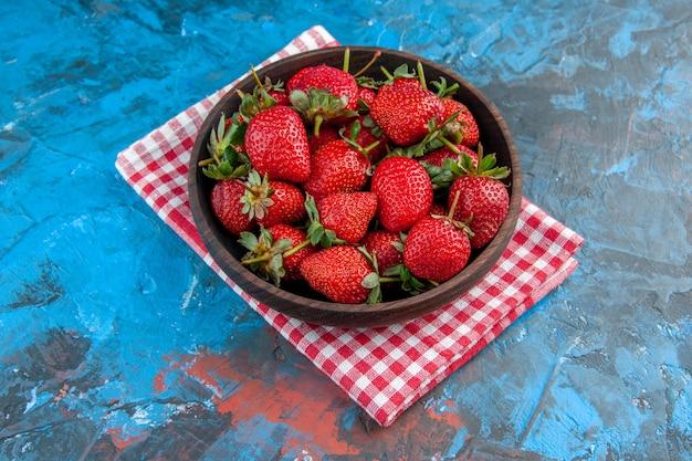 Halve bovenaanzichtplaat met aardbeien, vers, smakelijk, rijp fruit op blauwe achtergrond, zomerfoto, kleur, boom, rood, wilde bes