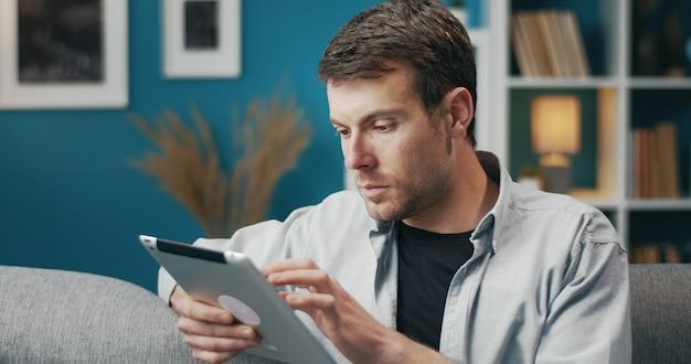 Halve draai portret van casual jongeman met behulp van tablet scherm zittend op de bank aan te raken