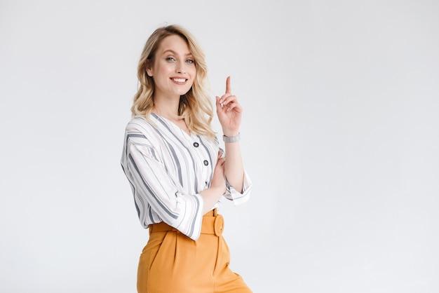 Halve draai portret van een jonge vrouw, gekleed in vrijetijdskleding glimlachend en wijzende vinger omhoog geïsoleerd over witte muur