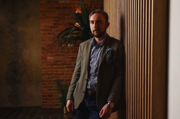Halve draai zelfverzekerde geconcentreerde knappe stoppels man in moderne groene jas staande bij de muur