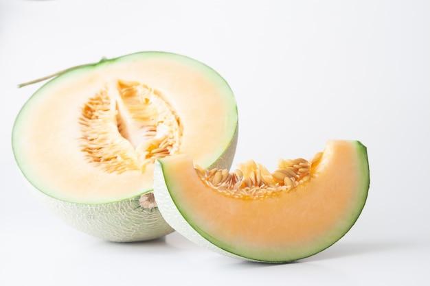 Halve en gesneden japanse meloenen die op witte achtergrond worden geïsoleerd. gezond fruit