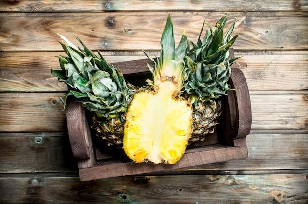 Halve en hele ananas in de doos. op houten