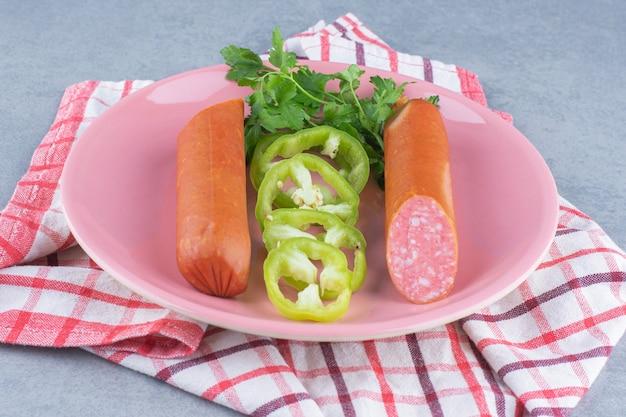 Halve gesneden salami op roze plaat.