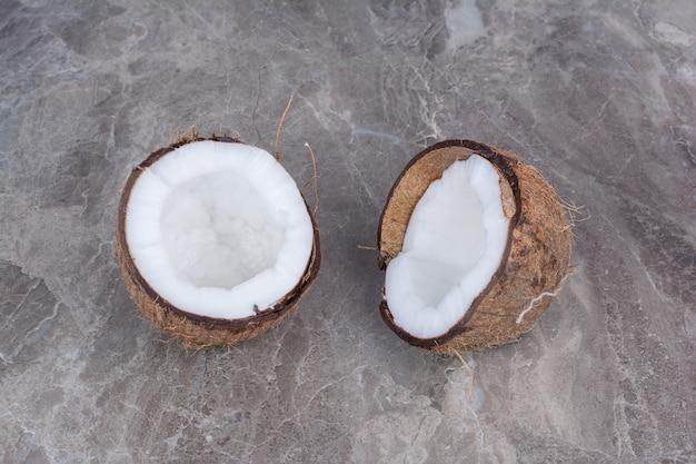 Halve gesneden verse kokosnoten op stenen achtergrond.