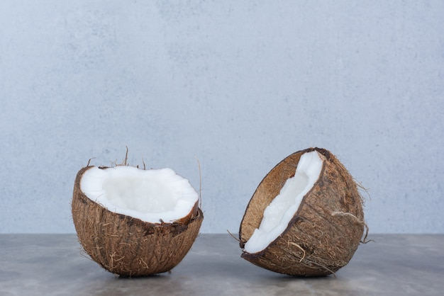Halve gesneden verse kokosnoten op stenen tafel.