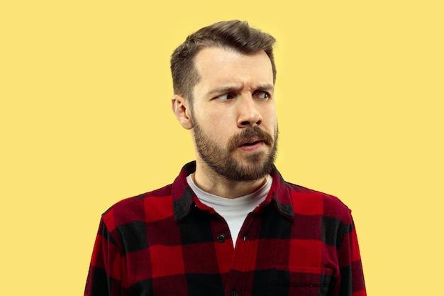 Halve lengte close-up portret van een jonge man in shirt op geel