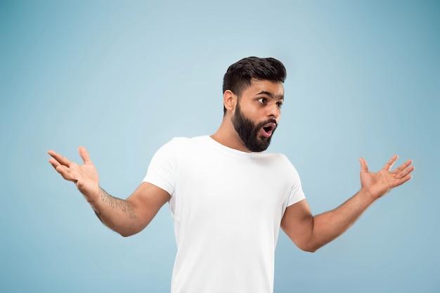 Halve lengte close-up portret van een jonge man in wit overhemd op blauwe muur