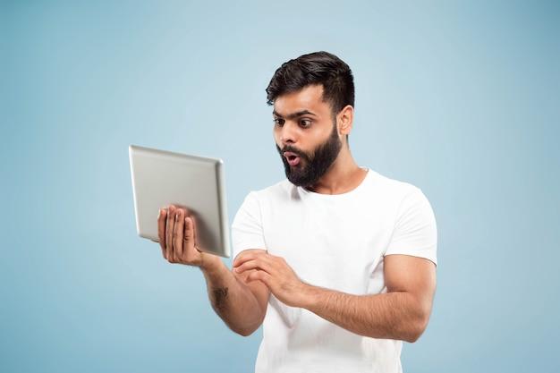 Halve lengte close-up portret van een jonge man op blauwe muur.