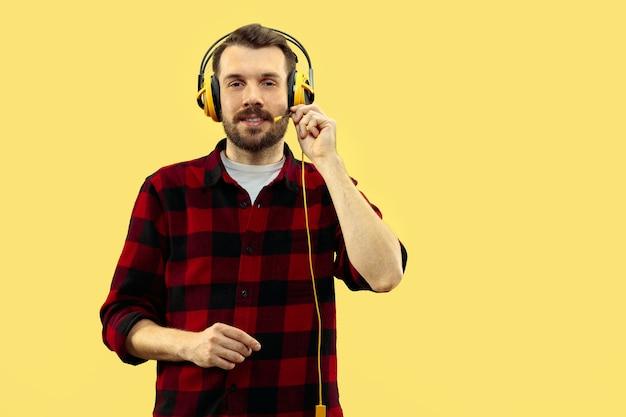 Halve lengte close-up portret van een jonge man op gele achtergrond.