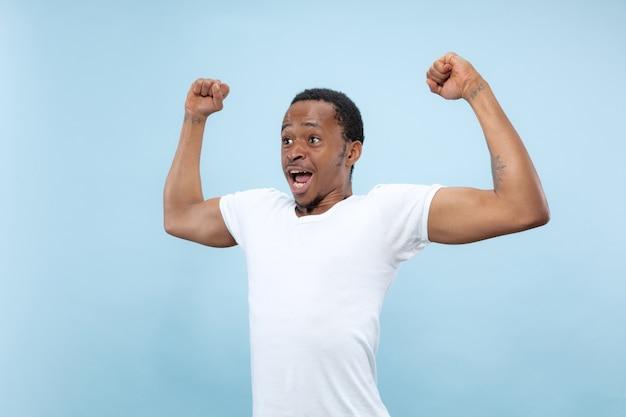 Halve lengte close-up portret van jonge afro-amerikaanse man in wit overhemd op blauwe achtergrond. menselijke emoties, gezichtsuitdrukking, advertentie, concept. vierend, verwonderd, verbaasd, geschokt, gek gelukkig.