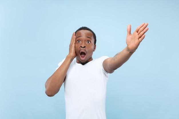 Halve lengte close-up portret van jonge afro-amerikaanse man in wit overhemd op blauwe achtergrond. menselijke emoties, gezichtsuitdrukking, advertentie, verkoopconcept. wijzen, kiezen, verwonderd. copyspace.