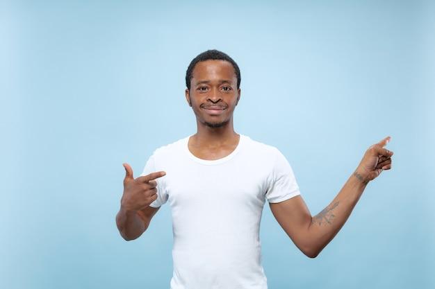 Halve lengte close-up portret van jonge afro-amerikaanse man in wit overhemd op blauwe achtergrond. menselijke emoties, gezichtsuitdrukking, advertentieconcept. lege balk tonen, wijzen, kiezen, uitnodigen.
