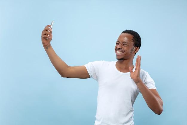 Halve lengte close-up portret van jonge afro-amerikaanse man in wit overhemd op blauwe achtergrond. menselijke emoties, gezichtsuitdrukking, advertentieconcept. selfie of content maken voor social media, vlog.