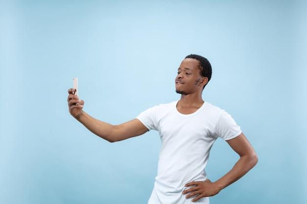 Halve lengte close-up portret van jonge afro-amerikaanse man in wit overhemd op blauwe muur. menselijke emoties, gezichtsuitdrukking, advertentieconcept. selfie of content maken voor sociale media, vlog.