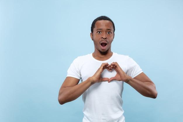 Halve lengte close-up portret van jonge afro-amerikaanse man in wit overhemd op blauwe muur. menselijke emoties, gezichtsuitdrukking, advertentieconcept. toont het teken oh een hart, verbaasd.