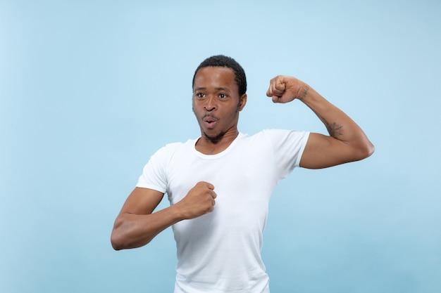 Halve lengte close-up portret van jonge afro-amerikaanse man in wit overhemd op blauwe ruimte. menselijke emoties, gezichtsuitdrukking, advertentie, concept