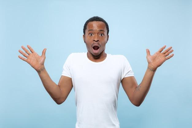 Halve lengte close-up portret van jonge afro-amerikaanse man in wit overhemd op blauwe ruimte. menselijke emoties, gezichtsuitdrukking, advertentie, verkoopconcept. uitnodigend, ziet er geschokt en verbaasd uit