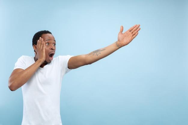 Halve lengte close-up portret van jonge afro-amerikaanse man in wit overhemd op blauwe ruimte. menselijke emoties, gezichtsuitdrukking, advertentie, verkoopconcept. wijzen, kiezen, verwonderd