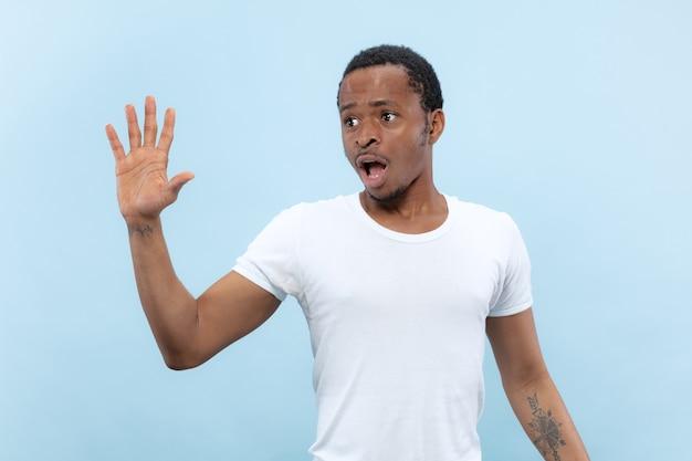 Halve lengte close-up portret van jonge afro-amerikaanse man in wit overhemd op blauwe ruimte. menselijke emoties, gezichtsuitdrukking, advertentie, verkoopconcept