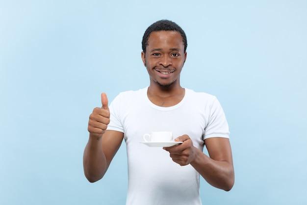Halve lengte close-up portret van jonge afro-amerikaanse man in wit overhemd op blauwe ruimte
