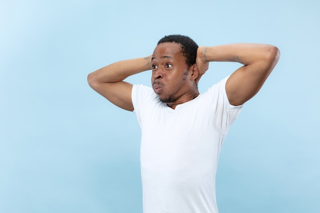 Halve lengte close-up portret van jonge afro-amerikaanse mannelijk model in wit overhemd op blauwe ruimte. menselijke emoties, gezichtsuitdrukking, advertentie of gokconcept
