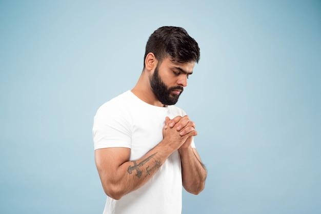 Halve lengte close-up portret van jonge hindoo man in wit overhemd geïsoleerd op blauwe achtergrond. menselijke emoties, gezichtsuitdrukking, advertentieconcept. negatieve ruimte. staan en bidden met gesloten ogen.
