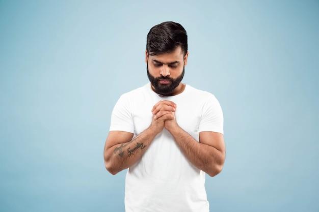 Halve lengte close-up portret van jonge hindoo man in wit overhemd geïsoleerd op blauwe muur. menselijke emoties, gezichtsuitdrukking, advertentieconcept. negatieve ruimte. staan en bidden met gesloten ogen.