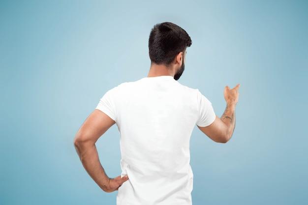 Halve lengte close-up portret van jonge hindoo man in wit overhemd op blauwe achtergrond. menselijke emoties, gezichtsuitdrukking, advertentieconcept. negatieve ruimte. lege balk tonen, wijzen, kiezen, uitnodigen.