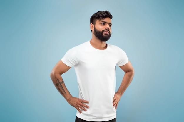 Halve lengte close-up portret van jonge hindoo man in wit overhemd op blauwe ruimte